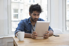 Asian man sitting at a table reading a Tablet PC. Stock Photo