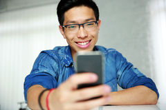 Asian man sitting at the table with smartphone Royalty Free Stock Photos
