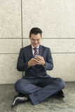 Asian man sitting with a tablet computer. Royalty Free Stock Photography