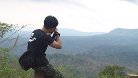 Asian man sitting at the wood chair and take a picture from top of mountain. Pang Sida National Park. Sakeao, Thailand stock video footage