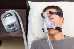 Asian man with sleep apnea using CPAP machine. Wearing headgear mask connecting to air tube stock photography
