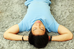 Asian man sleeping on the carpet. Young asian man sleeping on the carpet at home stock photography