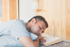 Reading book. Asian man sleeping after read book on his bed Royalty Free Stock Images