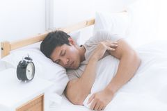 Asian man sleeping side way on white bed with alarm clock royalty free stock photos