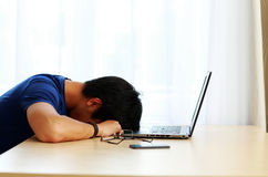 Asian man sleeping on the table with laptop Royalty Free Stock Images
