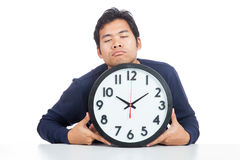 Asian man is sleepy with a clock Royalty Free Stock Images