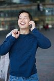 Asian man smiling with cellphone Royalty Free Stock Image