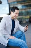 Asian man smiling with cellphone Royalty Free Stock Images