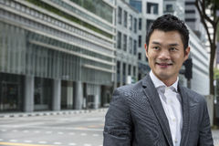 Asian man smiling & looking away with blurred office buildings as a background. Royalty Free Stock Photo