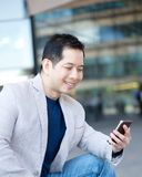 Asian man smiling with mobile phone Stock Images