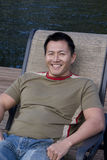 Asian Man Smiling and Resting. A casual happy Asian man sitting outdoors in a lounge chair royalty free stock photos
