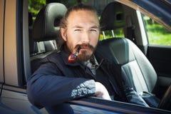 Asian man smoking pipe. Driver of modern car Stock Photography