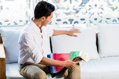 Asian man on sofa couch in furniture store Stock Image