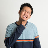 Asian man sore throat. With painful face expression, on plain background royalty free stock image