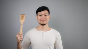 Asian man with spade of frying pan. Happy Asian man with spade of frying pan royalty free stock images