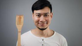 Asian man with spade of frying pan. Happy Asian man with spade of frying pan stock photography