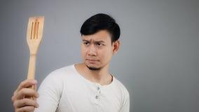 Asian man with spade of frying pan. Sad Asian man with spade of frying pan stock photos