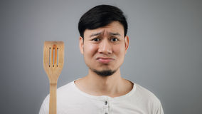 Asian man with spade of frying pan. Sad Asian man with spade of frying pan royalty free stock photos