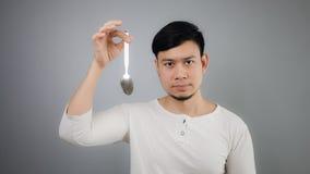 An Asian man with spoon. Asian man with spoon and grey background royalty free stock photo
