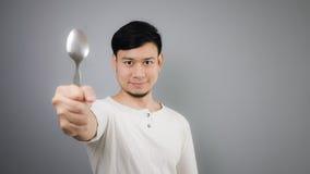 An Asian man with spoon. Asian man with spoon and grey background royalty free stock photos