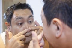 Asian Man Squeezing Acne on his Nose. Portrait of attractive young Asian man squeezing acne on his nose, mirror reflection in bathroom funny indonesian malaysian royalty free stock photography