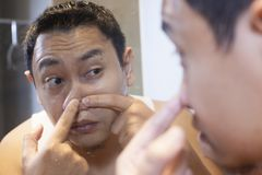 Asian Man Squeezing Acne on his Nose. Portrait of attractive young Asian man squeezing acne on his nose, mirror reflection in bathroom funny indonesian malaysian stock image