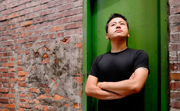 Asian man stand against a old door and lonely Stock Photo