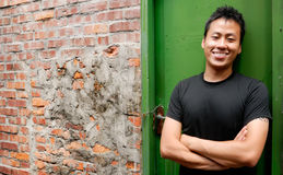 Asian man stand against a old door and smile. There is an Asian man stand against a old door and smile royalty free stock photo