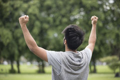 Asian man standing with arms raised outdoors. Stock Photography