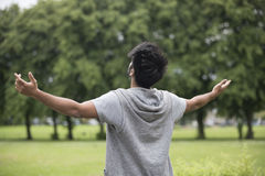 Asian man standing with arms raised outdoors. Royalty Free Stock Photography