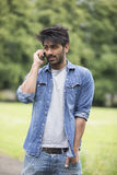 Asian Man standing in city park takling on mobile phone. Royalty Free Stock Photo