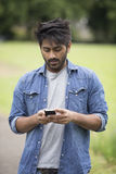 Asian Man standing in city park takling on mobile phone. Stock Photos