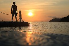 Asian man standing on floating pier at sunrise , Silhouette body of asian people early morning on the beach by the sea. Asian man standing and jumping on royalty free stock photo