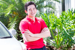 Asian man standing in front of car Stock Photo