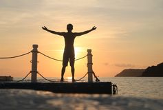 Asian man standing and jumping on floating pier at sunrise , Silhouette body of asian people early morning. On the beach by the sea royalty free stock photos