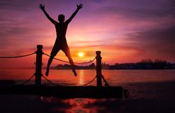 Asian man standing and jumping on floating pier at sunrise , Silhouette body of asian people early morning. On the beach by the sea royalty free stock photography