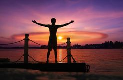 Asian man standing and jumping on floating pier at sunrise , Silhouette body of asian people early morning. On the beach by the sea stock photography