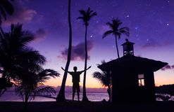 Asian man standing near the little hut on the coconut beach with a million stars and sunrise. Early morning royalty free stock photos