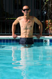 Asian man standing in swimming pool with arms on side Royalty Free Stock Image