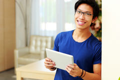 Asian man standing with tablet computer. Happy young asian man standing with tablet computer at home Royalty Free Stock Photography