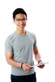 Asian man standing with tablet computer. Over white background Royalty Free Stock Photos