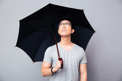 Asian man standing with umbrella and looking up Stock Photos