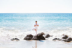 Asian man standing in yoga pose, on the beach Stock Images