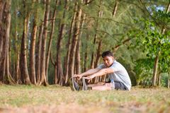 Asian man stretching body before running at the park and sunset time. stock photo