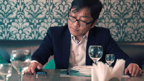 Asian man in suit businessman waiting in the cafe their food. Long waits for ordering. Nervous stock footage