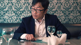 Asian man in suit businessman waiting in the cafe their food. Long waits for ordering. Nervous stock video