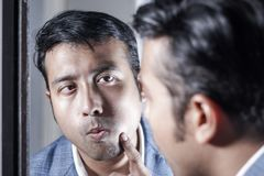 Asian man in suit looking after his appearance in front of a mirror beauty styling lifestyle. royalty free stock photo