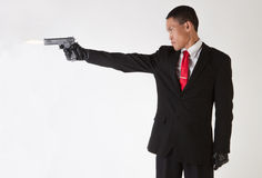 Asian Man in Suit and Tie Shooting Gun Royalty Free Stock Photography