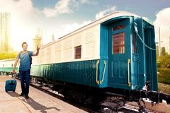 Asian man with suitcase bag and backpack standing and pointing a train wagon on station stock image