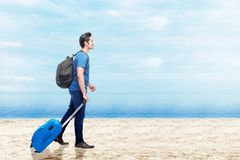 Asian man with suitcase bag and backpack walking on the beach stock images